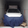 Transport a car in a shipping container
